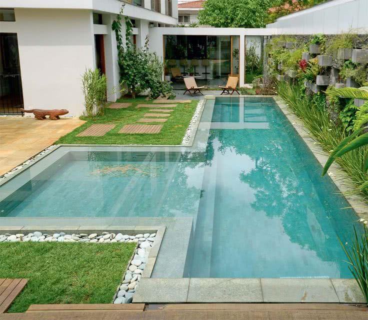 Les cailloux et les arbustes ajoutent à l'aménagement paysager de la piscine